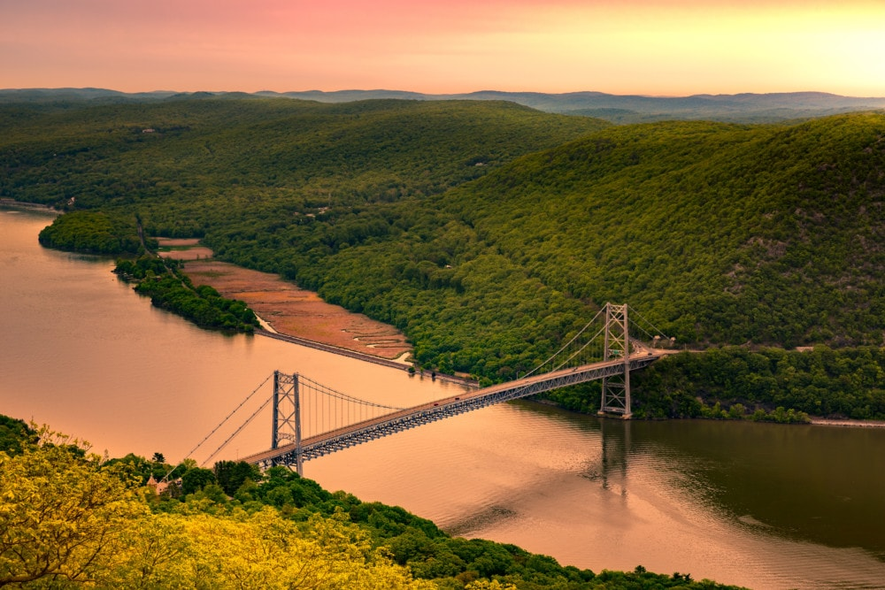 Aerial view of Bear Mountain Bridge at sunrise. Bear Mountain Bridge is a toll suspension bridge in New York State, carrying U.S. Highways 202 and 6 across the Hudson River